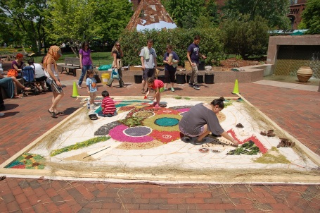 Visitors add natural materials to the ephemeral art piece at Garden Fest.