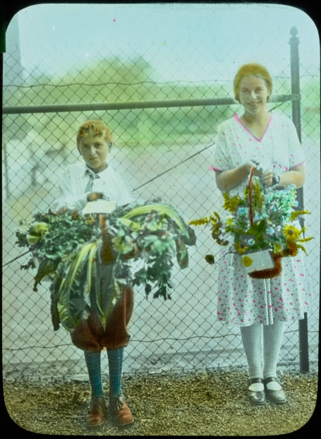 glass lantern slides of two students holding baskets of produce and flowers
